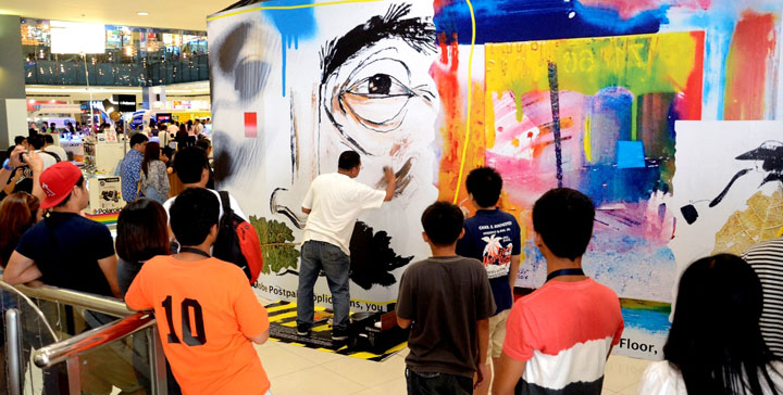 Mall goers at SM North Edsa stopped to watch how the artist add and transform the canvass into a one of a kind mural.