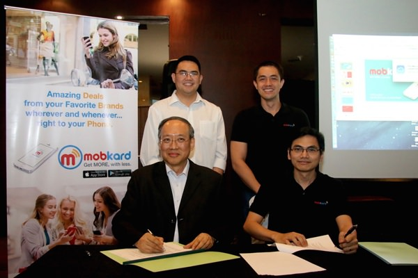 TheKard Inc. co-founders Francis Uy (seated, right) and Carlo Calimon (standing, right) seal the deal on additional funding for their startup, led by Globaltronics Inc. represented by its CEO William T. Guido (seated, left). Also in photo is IdeaSpace President Earl Martin Valencia. TheKard Inc. is part of the first batch of startups funded by IdeaSpace in 2013.