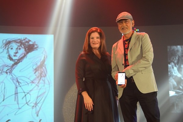 "Smart Infinity Head Julie Carceller with National Artist of the Philippines Benedicto Cabrera, famously known as ""BenCab,"" demonstrates the power of the Samsung Galaxy Note 5 as he did a quick digital artwork during the launch of Smart Infinity's 'trifecta' of new premium experiences"