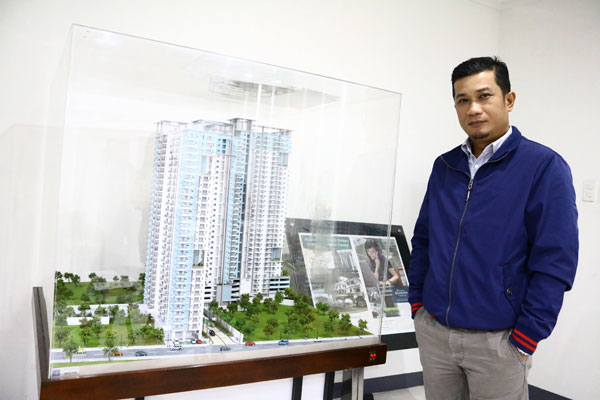 "Mr. Isaias ""Sonny"" Berdin, Jr., VP-Operations, Suntrust Properties, Inc. poses with a scale model of Suntrust Asmara, one of their projects located in Quezon City."