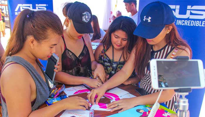 Beach-goers try to form the BeautyLive App logo as they are being livestreamed by the Zenfone Live