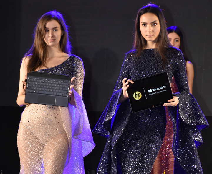 The new HP Spectre X2's keyboard base and tablet part held separately by two models, at the launch event at Okada Manila.