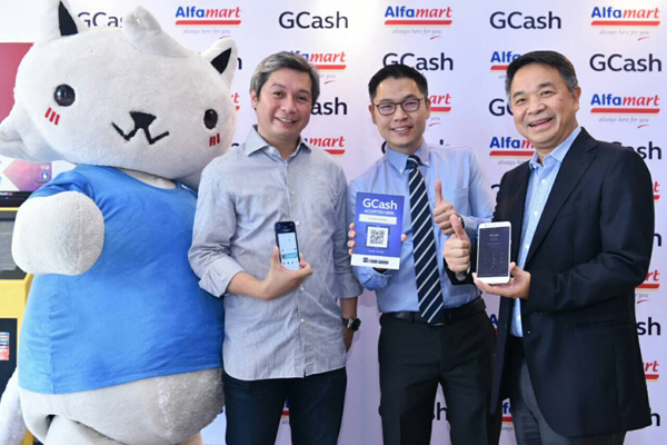 : In photo (from Left to Right) GCat, official mascot of GCash, Mynt Vice President for Business  Development Luigi Reyes, Alfamart Philippines' COO Harvey Ong and President Robert Kwee showing their GCash Mobile App and the official QR Code for Alfamart.