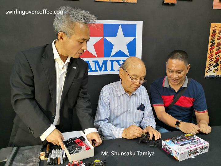 Master Modeller, President, and Chairman of Tamiya, Mr. Shunsaku Tamiya (center) signs a Mini4WD that Bam Amor (Tamiya Hobbyist and Tech Blogger) bought at the store. Mr. Tamiya is accompanied to his public appearance at the grand launch of The Brickyard by his interpreter (left most).