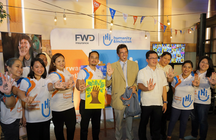 "FWD Insurance Community Care volunteers hold up their hands with the stylized ""Hi!"" for Humanity and Inclusion."